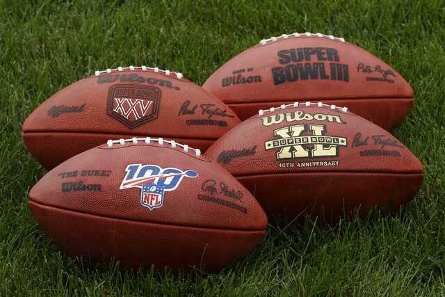 """In this Oct. 17, 2019, photo footballs are displayed at the Philadelphia Eagles's NFL football training facility in Philadelphia. Those shiny """"NFL 100"""" logos on all the footballs being used to commemorate the league's centennial season are part of a lengthy process that goes into making each handcrafted leather game ball. Wilson has been the official game ball of the NFL since 1941. The size, shape and feel of the football have evolved over the years, but the personal touch remains the same. (AP Photo/Matt Rourke)"""