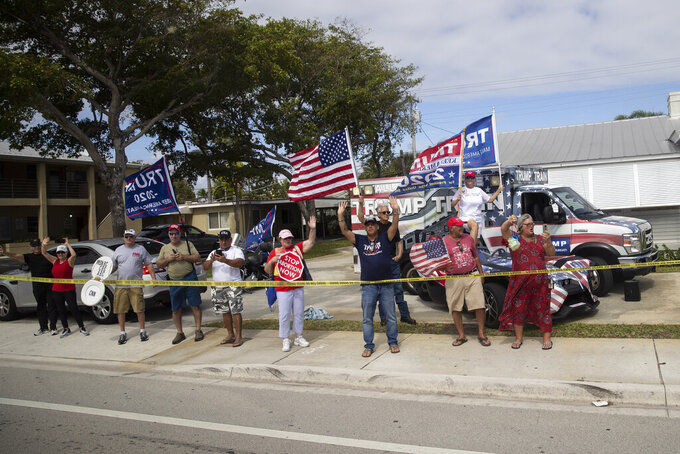 Supporters line the street as the motorcade for President Donald Trump, and first lady Melania Trump, passes en route to Air Force One at Palm Beach International Airport, Sunday, Feb. 16, 2020, in West Palm Beach, Fla. (AP Photo/Alex Brandon)