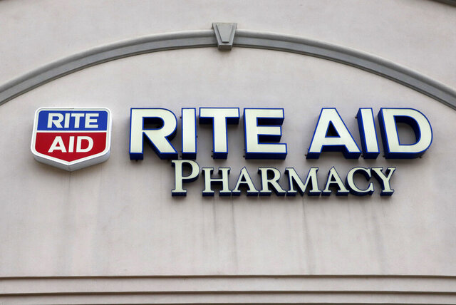 This is the sign on a Rite Aid Pharmacy in Pittsburgh, Pa., Tuesday, April 14, 2020.  Rite Aid topped Wall Street expectations for the fiscal second quarter, Thursday, Sept. 24,  and gave a revised annual forecast, one quarter after withdrawing it due to COVID-19 uncertainty. (AP Photo/Gene J. Puskar)