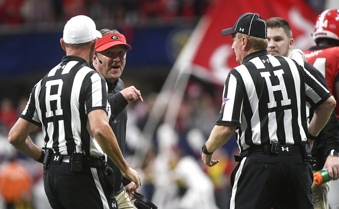 FILE - In this Dec. 1, 2018, file photo, Georgia head coach Kirby Smart, second from left,  speaks with officials during the first half of the Southeastern Conference championship NCAA college football game against Alabama, in Atlanta. The Southeastern Conference hired international accounting firm Deloitte to conduct a review of its football officiating. Commissioner Greg Sankey says the move was a reaction in part to the often opinionated view of referees by the public and media. (AP Photo/John Amis, File)