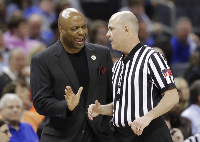 Florida State head coach Leonard Hamilton, left, argues a call during the first half of an NCAA college basketball game against Virginia in the Atlantic Coast Conference tournament in Charlotte, N.C., Friday, March 15, 2019. (AP Photo/Chuck Burton)