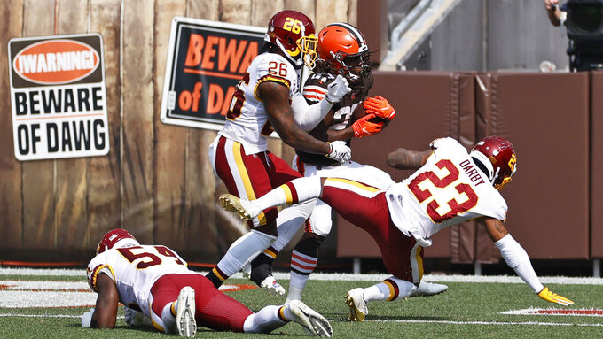 Cleveland Browns running back Kareem Hunt, center, scores on a 9-yard pass reception during the first half of an NFL football game against the Washington Football Team, Sunday, Sept. 27, 2020, in Cleveland. (AP Photo/Ron Schwane)
