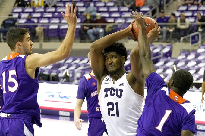 Northwestern State guard Jovan Zelenbaba (15) and guard LaTerrance Reed (1) defend as TCU center Kevin Samuel (21) attempts to make a pass during the second half of an NCAA college basketball game in Fort Worth, Texas, Thursday, Dec. 3, 2020. (AP Photo/Tony Gutierrez)