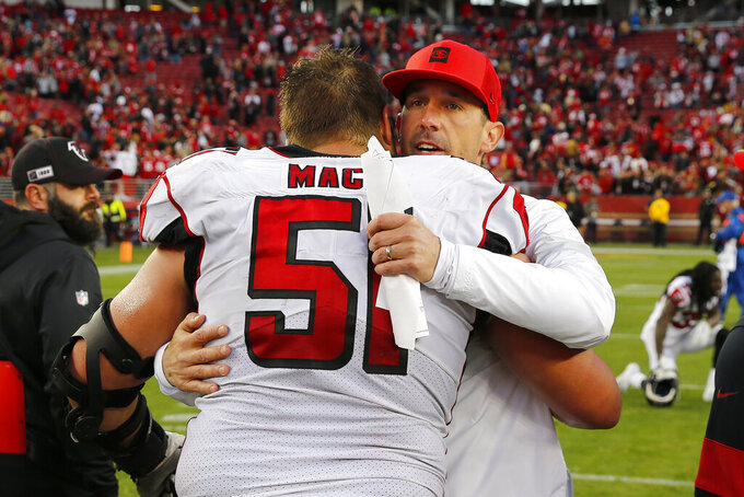 San Francisco 49ers head coach Kyle Shanahan, right, hugs Atlanta Falcons center Alex Mack (51) after an NFL football game in Santa Clara, Calif., Sunday, Dec. 15, 2019. (AP Photo/John Hefti)