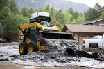 A bobcat moves a wet slurry of ash, mud and forest debris into a pile to be removed after the muck was left behind from flooding caused by a monsoon rain event over the 2019 Museum Fire burn area in Flagstaff, Ariz., on Wednesday, July 14, 2021. The threat of flash flooding will remain through next week, the National Weather Service said, though the coverage will be more scattered than widespread. (Jake Bacon/Arizona Daily Sun via AP)