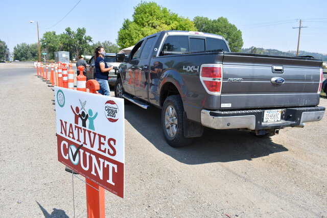 Vehicles stop at a drive-thru U.S. Census participation campaign organized by Montana Native Vote on the Crow Indian Reservation in Lodge Grass, Mont. on Wednesday, Aug. 26, 2020. There have always been geographic and cultural challenges to Census taking on Native lands, but the pandemic dealt a devastating setback. (AP Photo/Matthew Brown)
