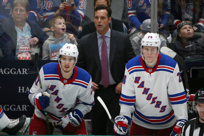 FILE - New York Rangers head coach David Quinn watches his team play against the Dallas Stars with center Brett Howden (21) and right wing Kaapo Kakko (24) during the third period of an NHL hockey game in Dallas, in this Tuesday, March 10, 2020, file photo. The New York Rangers fired coach David Quinn and three assistant coaches Wednesday, May 12, 2021, after missing the playoffs with one of the NHL's up-and-coming young teams.  (AP Photo/Michael Ainsworth, File)