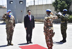 In this photo released by Lebanon's official government photographer Dalati Nohra, Lebanese Prime Minister Hassan Diab, center, stands next to the Head of Mission and Force Commander of the United Nations Interim Force in Lebanon, Major-General Stefano Del Col, left, as he reviews the honor guard of the United Nations peacekeepers, upon his arrival at their headquarters, in the southern coastal border town of Naqoura, Lebanon, Wednesday, May 27, 2020. The visit comes against the backdrop of a war of words between Israel and Lebanese officials, including the powerful Hezbollah group, over the mandate of the U.N. troops, known as UNIFIL, deployed in southern Lebanon since an Israel invasion in 1978. (Dalati Nohra via AP)