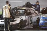 AJ Allmendinger's crew members cover his car on pit road during a rain delay at the NASCAR Xfinity Series auto race at Daytona International Speedway, Friday, Aug. 27, 2021, in Daytona Beach, Fla. (AP Photo/Phelan M. Ebenhack)