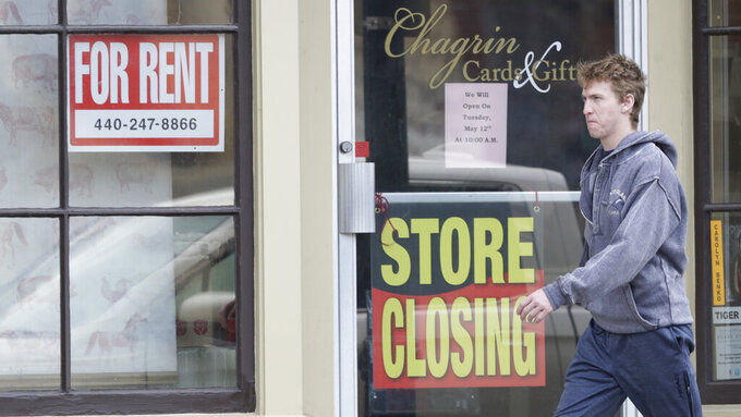 A man walks past a closed business, Wednesday, April 29, 2020, in Chagrin Falls, Ohio. The U.S. economy shrank at a 4.8% annual rate last quarter as the coronavirus pandemic shut down much of the country and began triggering a recession that will end the longest expansion on record. (AP Photo/Tony Dejak)