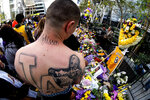 FILE - In this Jan. 27, 2020, file photo, Rudy Bermudez with a tattoo of the late Kobe Bryant on his back looks at a memorial for Bryant near Staples Center in Los Angeles. (AP Photo/Ringo H.W. Chiu, File)