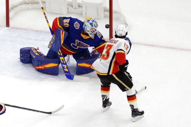 Calgary Flames' Johnny Gaudreau (13) shoots wide of St. Louis Blues goaltender Jordan Binnington during the second period of an NHL hockey game Thursday, Nov. 21, 2019, in St. Louis. (AP Photo/Jeff Roberson)