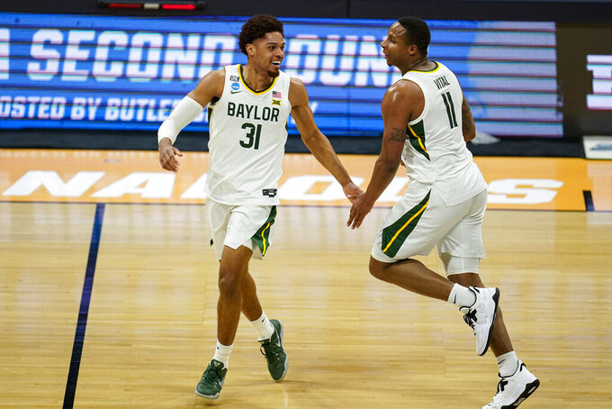 Baylor 's Mark Vital (11) celebrates a dunk with MaCio Teague (31) in the first half of a second-round game in the NCAA men's college basketball tournament at Hinkle Fieldhouse in Indianapolis, Sunday, March 21, 2021. (AP Photo/Michael Conroy)