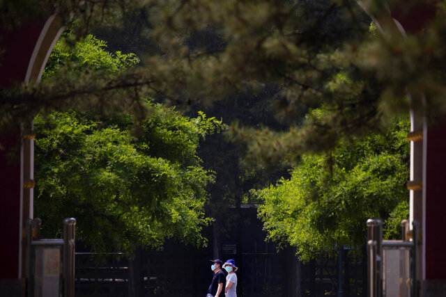 People wear face masks to protect against the new coronavirus as they walk through a public park in Beijing, Saturday, May 2, 2020. China, where the pandemic began in December, reported one new infection and no deaths in the 24 hours through midnight Friday. (AP Photo/Mark Schiefelbein)