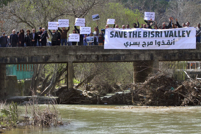 Lebanese protesters hold placards during a protest against the Bisri dam project, in the Bisri Valley, 58 kilometers (36 miles) southeast of Beirut, Lebanon, Sunday, March. 10, 2019. The valley of Bisri in Lebanon lies on a green fertile bed, a spot that has cradled civilizations dating as far back as the Bronze Age. Its expansive lands of pine, citrus trees and ancient ruins are about to turn into a controversial mega dam funded by the World Bank. For years now, activists and locals have voiced their opposition to what they describe as not only