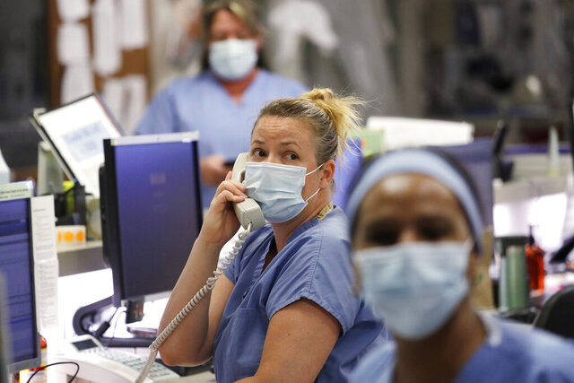 FILE - In this May 8, 2020, file photo, registered nurse Katie Hammond looks up as she talks on the phone in the COVID-19 Intensive Care Unit at Harborview Medical Center, which is part of Seattle-area health care system UW Medicine, in Seattle. UW Medicine, which has played a leading role in responding to the coronavirus outbreak, is now facing a huge financial hole because of the fallout from COVID-19. The Seattle Times reports UW Medicine's losses could be more than $500 million by the end of the summer. (AP Photo/Elaine Thompson, File)