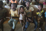 Children sit on benches in a hall while waiting to receive food and drinking water at a temporary shelter for children in Pemba city, on the northeastern coast of Mozambique, Thursday May 2, 2019. More than 1 million children have been affected by a pair of cyclones that ripped into Mozambique in less than two months, the United Nations children's agency says, and now many of the children are without shelter or food. (AP Photo/Tsvangirayi Mukwazhi)