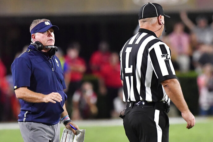 Notre Dame head coach Brian Kelly speaks to an offical during the first half of an NCAA college football game against Georgia, Saturday, Sept. 21, 2019, in Athens, Ga. (AP Photo/Mike Stewart)