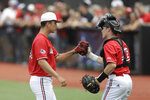 Louisville's Bobby Miller, left, is greeted by Henry Davis during the eighth inning in Game 2 of an NCAA college baseball super regional tournament against East Carolina, Saturday, June 8, 2019, in Louisville, Ky. Louisville won 12-0. (AP Photo/Darron Cummings)