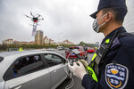 In this Tuesday, Feb. 11, 2020, photo released by China's Xinhua News Agency, a police officer operates a drone carrying a QR code placard near an expressway toll station in Shenzhen in southern China's Guangdong Province. As a measure to help prevent and control novel coronavirus, an online register system for vehicles coming back to Shenzhen has been put into use since Feb. 8. To increase the efficiency, local police officers used drones to carry a QR code at the expressway exits for drivers to get registered with less contact with other people. (Lai Li/Xinhua via AP)