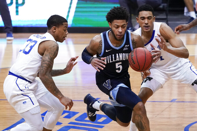 Villanova guard Justin Moore (5) drives against Seton Hall guards Shavar Reynolds (33) and Jared Rhoden during the second half of an NCAA college basketball game, Saturday, Jan. 30, 2021, in Newark, N.J. (AP Photo/Mary Altaffer)