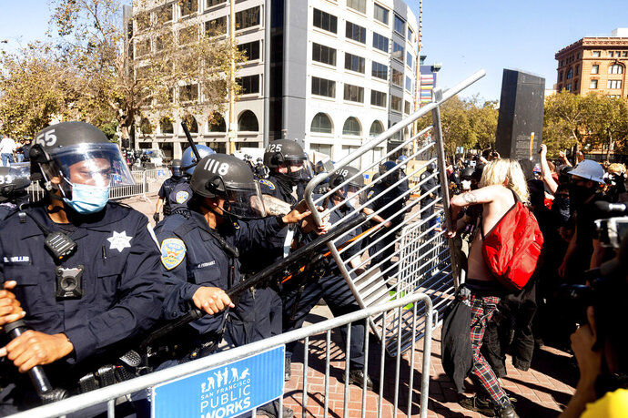 Police officers to to hold off counter-protesters as conservative activists stage a free speech rally in San Francisco on Saturday, Oct. 17, 2020. About a dozen pro-Trump demonstrators were met by several hundred counter-protesters as they tried to rally. (AP Photo/Noah Berger)