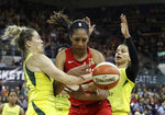 Las Vegas Aces' A'ja Wilson, center, fights for a loose ball with Seattle Storm's Sami Whitcomb, left, and Alysha Clark during the first half of a WNBA basketball game Friday, July 19, 2019, in Seattle. (AP Photo/Elaine Thompson)