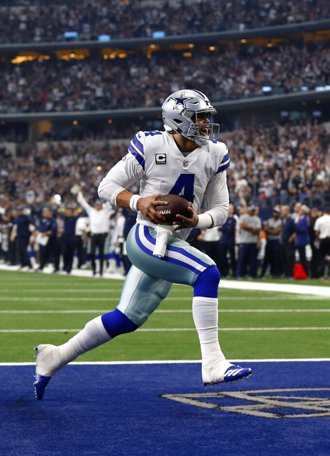 FILE - In this Dec. 23, 2018, file photo, Dallas Cowboys quarterback Dak Prescott (4) scores a touchdown on a running play during the team's NFL football game against the Tampa Bay Buccaneers in Arlington, Texas. The Cowboys have been at their best when NFL rushing champion Ezekiel Elliott dictates the pace, allowing Prescott's passing game to be a complementary piece. (AP Photo/Roger Steinman, File)