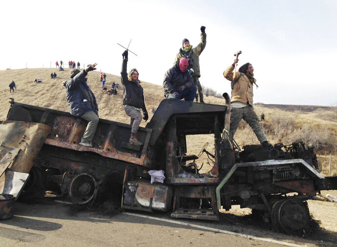 FILE - In this Nov. 21, 2016 file photo, protesters against the Dakota Access oil pipeline stand on a burned-out truck near Cannon Ball, N.D. Standing Rock Sioux tribal members and others who're suing over a five-month shutdown of a North Dakota highway during protests against the Dakota Access oil pipeline have broadened their claims against state and county government officials. They now allege the closure was not only aimed at protesters but also at influencing the tribe's position on the camps and the media's coverage of the prolonged clash. Authorities dispute the new claims. (AP Photo/James MacPherson, File)
