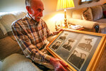 Loyd W. Brandt holds a picture of he and his five brothers, all of whom served in the US Marine Corps during WWII, at his home on Wednesday, Sept. 11, 2019,  in Rapid City, S.D. Wartime reunions or near-reunions with Loyd's many Brandt brothers provide a kind of mortar for these martial tales, juxtaposing family with war. Six of seven Brandt brothers from South Dakota served with the Marines in the South Pacific — five after Pearl Harbor. One died there. Another survived his severe wounds to reach old age.  (Adam Fondren/Rapid City Journal via AP)