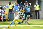 Carolina Panthers wide receiver D.J. Moore (12) makes a catch in front of Los Angeles Chargers cornerback Michael Davis during the second half of an NFL football game Sunday, Sept. 27, 2020, in Inglewood, Calif. (AP Photo/Alex Gallardo)