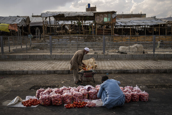 An Afghan man sells fruit on a street in Kabul, Afghanistan, Wednesday, Sept. 22, 2021. (AP Photo/Bernat Armangue)