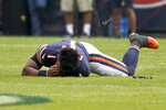 Chicago Bears quarterback Justin Fields holds his head after being tackled after have his helmet knocked off during the second half of an NFL preseason football game against the Buffalo Bills Saturday, Aug. 21, 2021, in Chicago. The Bills won 41-15. (AP Photo/Nam Y. Huh)