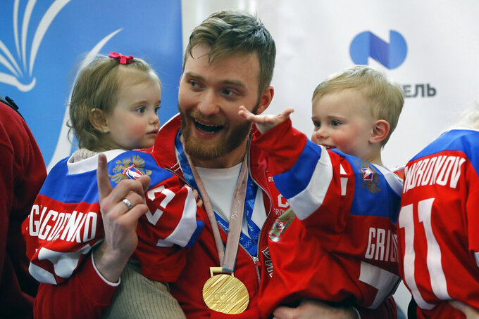 FILE - In this Feb. 26, 2018, file photo, Russian ice hockey player Mikhail Grigorenko holds his children after arriving at Sheremetyevo airport, outside Moscow, Russia from the Olympics in Pyeongchang, South Korea. Blue jackets general manager Jarmo Kekalainen announced the signing Monday, April 20, 2020, of forward Mikhail Grigorenko to a one-year contract for the 2020-21 season. A person with knowledge of the contract says it's worth $1.2 million. The person spoke to The Associated Press on condition of anonymity because the team does not release contract terms.(AP Photo/Pavel Golovkin, File)