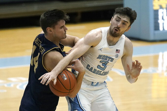 Notre Dame forward Nate Laszewski (14) pressures North Carolina guard Andrew Platek (3) during the first half of an NCAA college basketball game in Chapel Hill, N.C., Saturday, Jan. 2, 2021. (AP Photo/Gerry Broome)