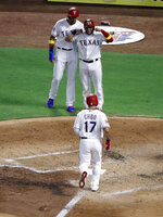Texas Rangers' Shin-Soo Choo approaches the plate after hitting a three-run home run against the Oakland Athletics that scored Ronald Guzman, left rear, and Jose Trevino during the second inning of a baseball game in Arlington, Texas, Friday, Sept. 13, 2019. (AP Photo/Tony Gutierrez)