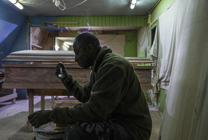 Haitian migrant and coffin factory worker Francois Joseph eats his lunch at the Bergut Funeral Services factory in Santiago, Chile, Thursday, June 18, 2020. The coffin production has had to increase up to 120%, according to Nicolas Bergerie, owner of the factory. His more basic coffin model is called the COVID model and is made to cope with the increase of deaths during the coronavirus pandemic. (AP Photo/Esteban Felix)