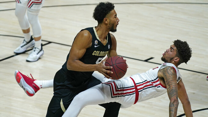Colorado guard D'Shawn Schwartz (5) commits a charge against Utah forward Timmy Allen, right, in the first half during an NCAA college basketball game Monday, Jan. 11, 2021, in Salt Lake City. (AP Photo/Rick Bowmer)