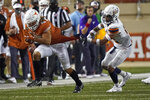 Texas's Jordan Whittington (4) tries to escape UTEP's Tyson Wilson (2) during the first half of an NCAA college football game in Austin, Texas, Saturday, Sept. 12, 2020. (AP Photo/Chuck Burton)