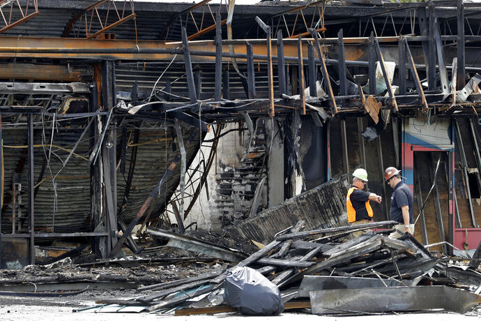 Two workers inspect the damage to a sporting goods store, Monday, June 1, 2020, in Tampa, Fla., after the establishment was looted and burned by protesters during a demonstration Saturday night. Several counties across Florida issued curfews to curb large crowds gathering to protest the killings of black people by police. (AP Photo/Chris O'Meara)