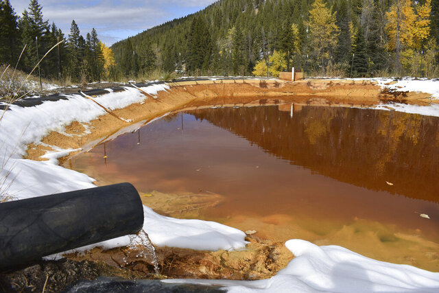FILE - In this Oct. 12, 2018 file photo, water contaminated with arsenic, lead and zinc flows from a pipe out of the Lee Mountain mine and into a holding pond near Rimini, Mont. The community is part of the Upper Tenmile Creek Superfund site, where dozens of abandoned mines have left water supplies polluted and residents must use bottled water. The Trump administration has built up the largest backlog of unfunded toxic Superfund projects awaiting clean-up in at least 15 years, nearly tripling the number of sites where clean-ups are ready to go but awaiting money, according to 2019 figures quietly released by the Environmental Protection Agency over the winter holidays. (AP Photo/Matthew Brown)