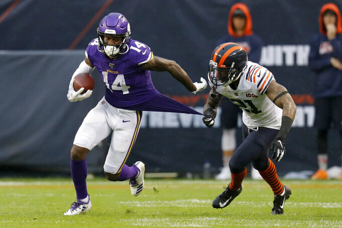 Minnesota Vikings wide receiver Stefon Diggs (14) runs with the ball as Chicago Bears strong safety Ha Ha Clinton-Dix (21) tugs on Diggs' jersey during the second half of an NFL football game Sunday, Sept. 29, 2019, in Chicago. The Bears won 16-6. (AP Photo/Charles Rex Arbogast)