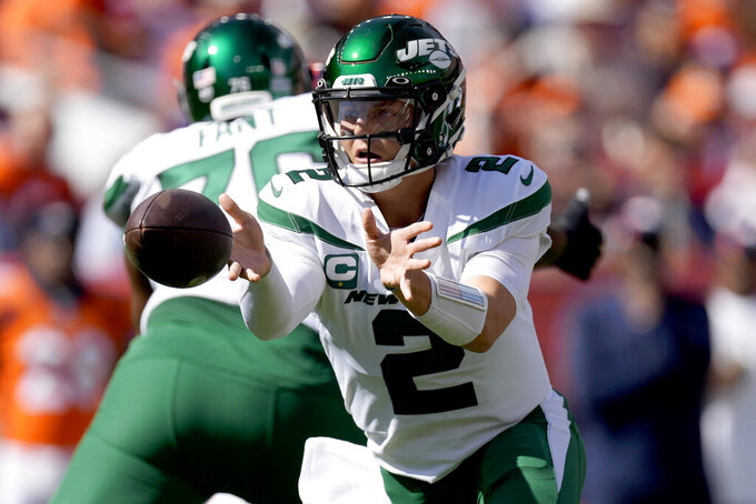 New York Jets quarterback Zach Wilson (2) hands off against the Denver Broncos during the first half of an NFL football game, Sunday, Sept. 26, 2021, in Denver. (AP Photo/David Zalubowski)