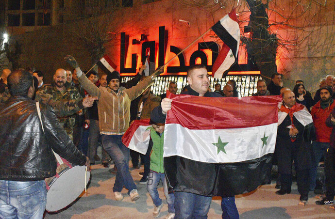 In this photo released by the Syrian official news agency SANA, Syrians celebrate as they hold their national flags in Aleppo province, Syria, Monday, Feb. 17, 2020. On Monday Syria's military announced its troops have regained control of territories in northwestern Syria