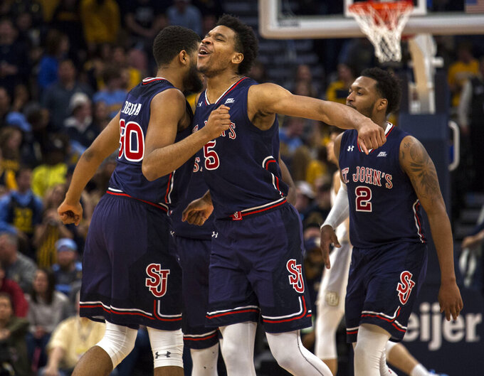 St. John's guard Justin Simon, center, is congratulated by teammates after a dunk against Marquette during the first half of an NCAA college basketball game Tuesday, Feb. 5, 2019, in Milwaukee. (AP Photo/Darren Hauck)