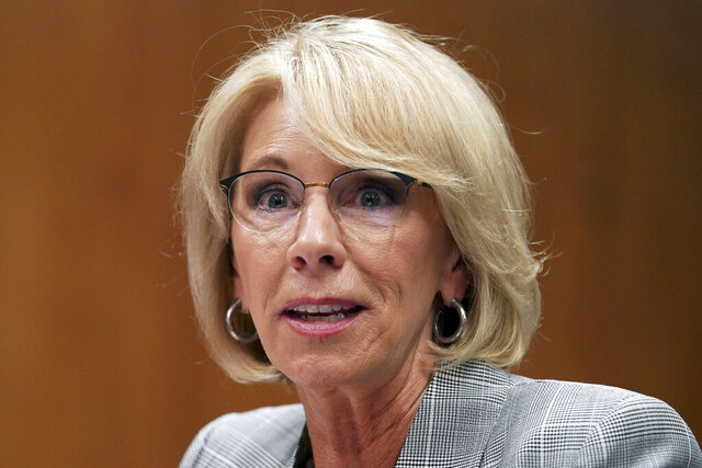 FILE - In this June 5, 2018, file photo, Education Secretary Betsy DeVos testifies during a Senate Subcommittee on Labor, Health and Human Services, Education, and Related Agencies Appropriations in Washington. Facing a federal lawsuit and mounting pressure to act, Education Secretary Betsy DeVos on Friday, Nov. 8, 2019, said she will forgive loans for more than 1,500 borrowers who attended a pair of for-profit colleges that shut down last year.  (AP Photo/Carolyn Kaster, File)