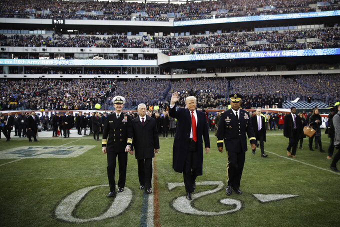 President Donald Trump, center right, accompanied by Secretary of Defense Jim Mattis, center left, waves as they walk on the field before of an NCAA college football game between Army and Navy, Saturday, Dec. 8, 2018, in Philadelphia. (AP Photo/Matt Rourke)