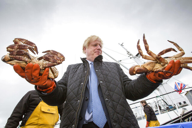 Britain's Prime Minister Boris Johnson holds crabs caught on the Carvela with Karl Adamson at Stromness Harbour in Stromness, Orkney, Scotland, during a visit to the Highlands and Northern Isles of Scotland, Thursday July 23, 2020. (Robert Perry/PA via AP)