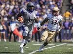 James Madison running back Trai Sharp (1) is chased down by Elon running back Brelynd Cyphers (33) during the first half of an NCAA college football game in Harrisonburg, Va., Saturday, Oct. 6, 2018. (Daniel Lin/Daily News-Record via AP)