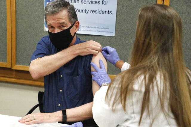 Michelle Winings, R.N., prepares to give Gov. Roy Cooper his flu shot at the Wake County Health Department in Raleigh, N.C., Friday, Sept. 25, 2020. (Ethan Hyman/The News & Observer via AP)